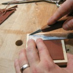 Fitting a leather square to a carcase bottom panel.