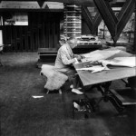 Frank Lloyd Wright working at drafting table.